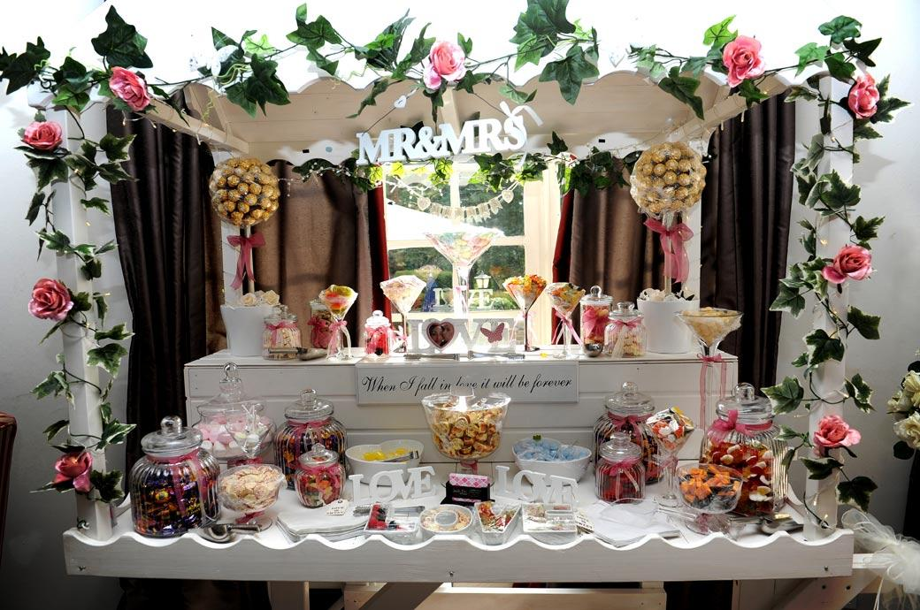 Welcoming wedding picture of a bright, colourful and full of sweets Candy cart set up especially for the children in The Lounge at the Gorse Hill Surrey wedding venue