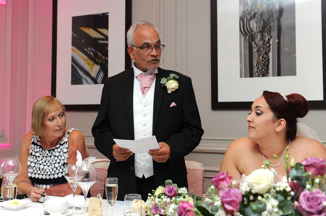 Father of the Bride catches the attention of the head table during the wedding speeches captured in this picture at Surrey Gorse Hill in The Restaurant
