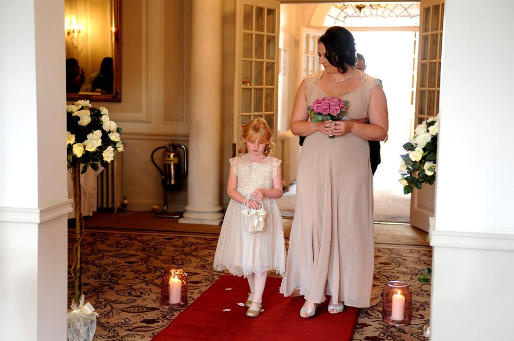 Bridesmaid looks down to the flower girl as they walk down the red carpet in the lounge at wedding venue Gorse Hill Surrey at the start of the marriage ceremony