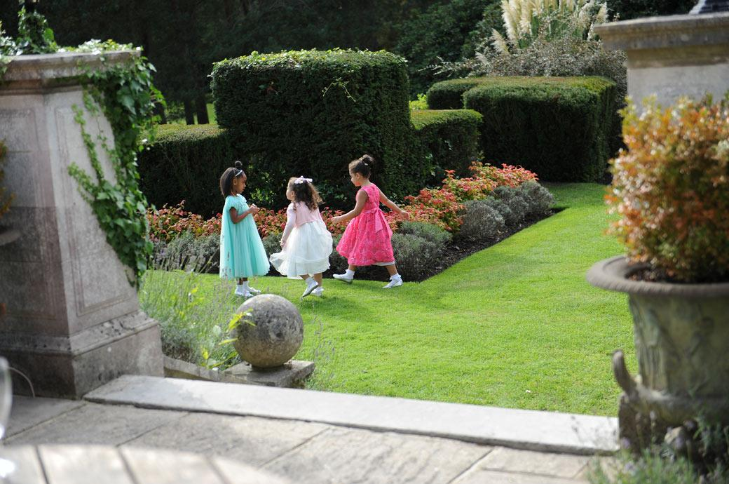 A captured scene from a wedding reception at the popular Gorse Hill venue in Woking Surrey of sweet little girls in their pretty colourful dresses playing on the lawn