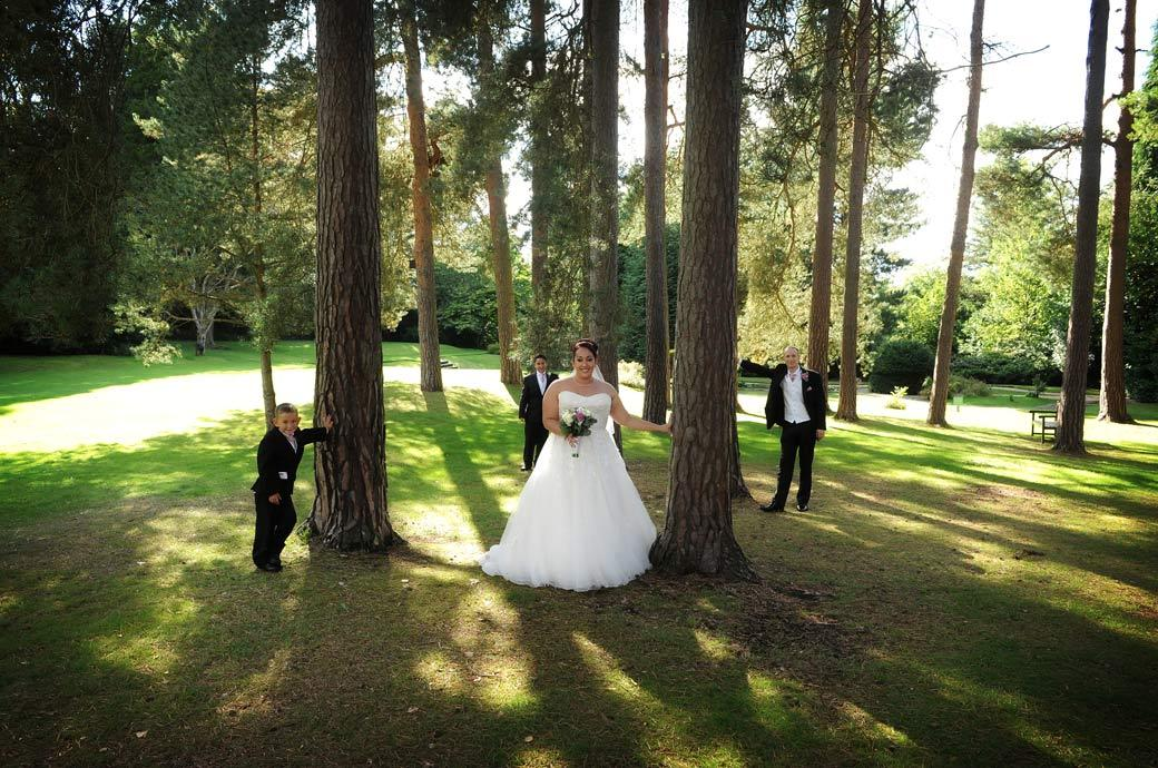 Fun wedding photo of the Bride and Groom striking a pose with their two sons under the trees in the grounds of wedding venue Gorse Hill in Surrey Woking