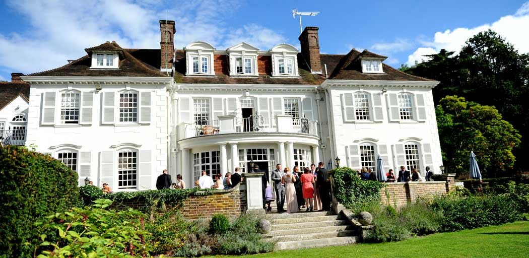 Welcoming  and relaxed Gorse Hill in Woking is a grand looking and yet intimate Surrey wedding venue as captured outside in this wedding photograph during the drinks reception