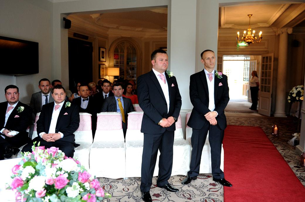 Solemn and serious looking Groom and best man standing in the marriage ceremony room at Surrey wedding venue Gorse Hill Woking awaiting the entrance of the Bride