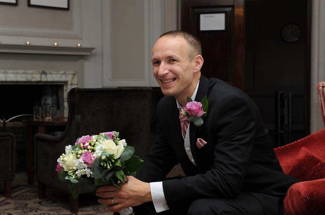Light-hearted and fun wedding photo of the Groom relaxing in The Lounge holding his wife's wedding bouquet at Gorse Hill in Surrey before being announced for dinner