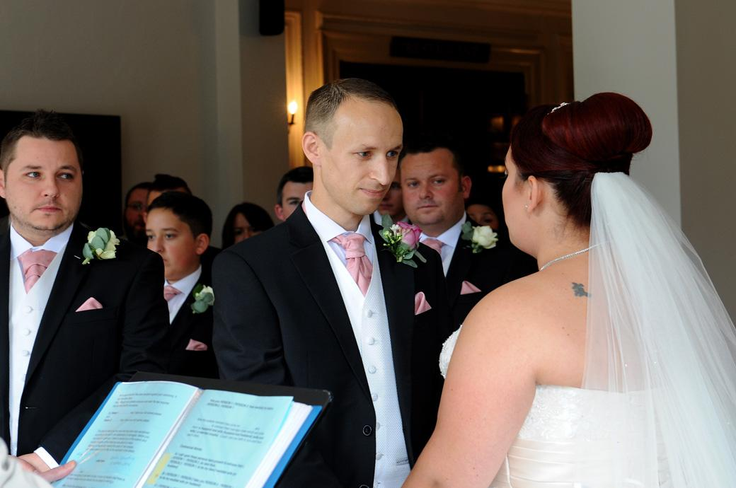 Wedding photograph of the Groom looking intently at his bride during the marriage ceremony at wedding venue Gorse Hill in Surrey as his best man looks on