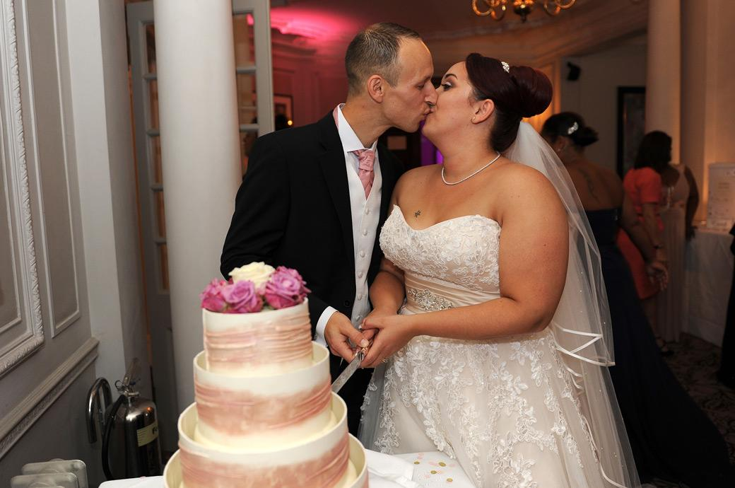 Bride and Groom have a passionate kiss before cutting their wedding cake captured at the lovely Surrey wedding venue Gorse Hill during the evening reception