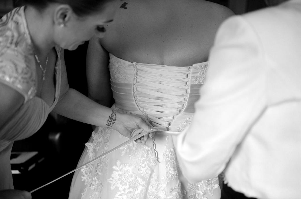 Close  up wedding photo of a bridesmaid lacing up the ribbons of the Bride's dress captured by a Surrey Lane wedding photographer at Gorse Hill in the bridal suite