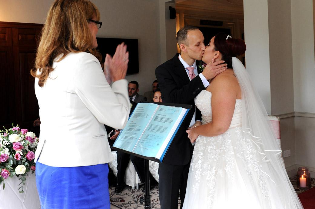 Bride and Groom kiss passionately in The Lounge ceremony room at the popular Gorse Hill wedding venue in Surrey after being announced Husband and Wife