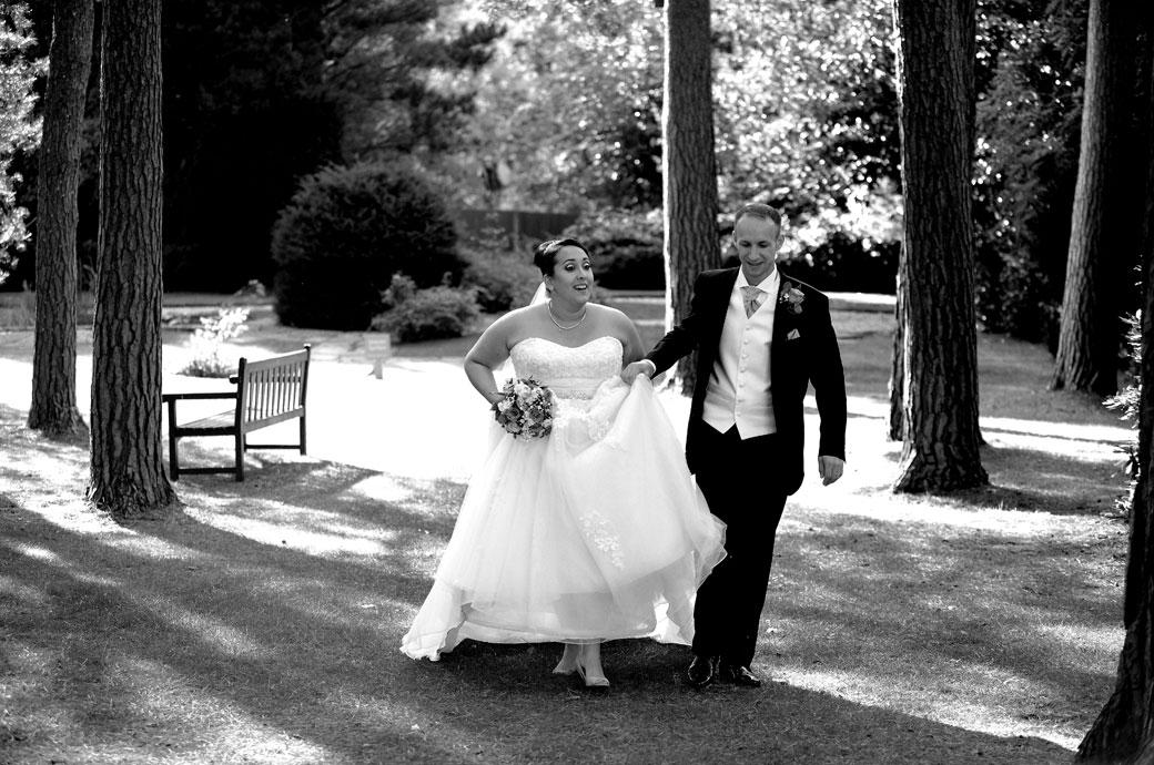 Groom helps his Bride with her dress as they walk across the lawn after a romantic walk with their Surrey Lane wedding photographer in the lovely Gorse Hill venue grounds