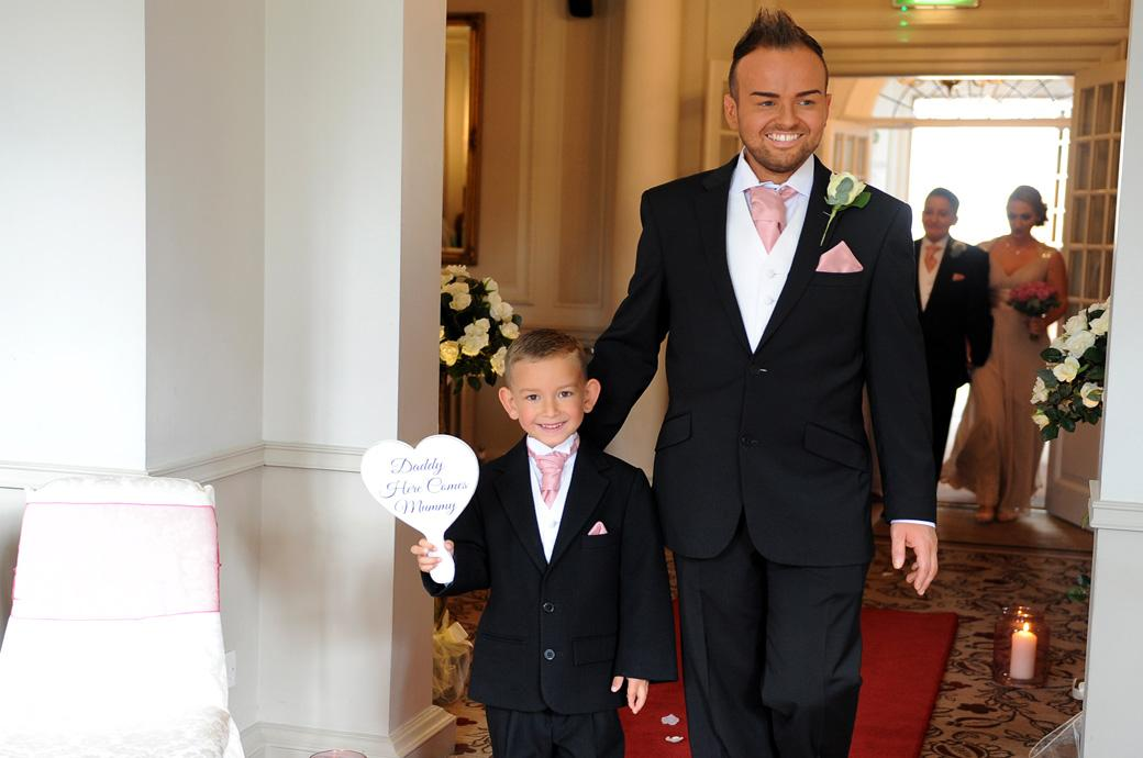 Groomsman escorts a smiling pageboy holding up his message to daddy sign as they walk down the red carpet at the start of the marriage ceremony at Gorse Hill Woking Surrey