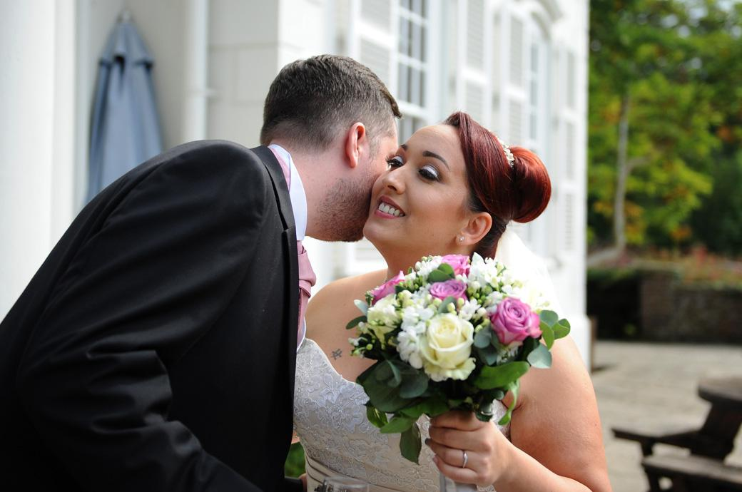 Groomsman congratulates the beaming Bride with a small kiss out on the patio after the service captured by a Surrey Lane wedding photographer at the Gorse Hill venue in Woking