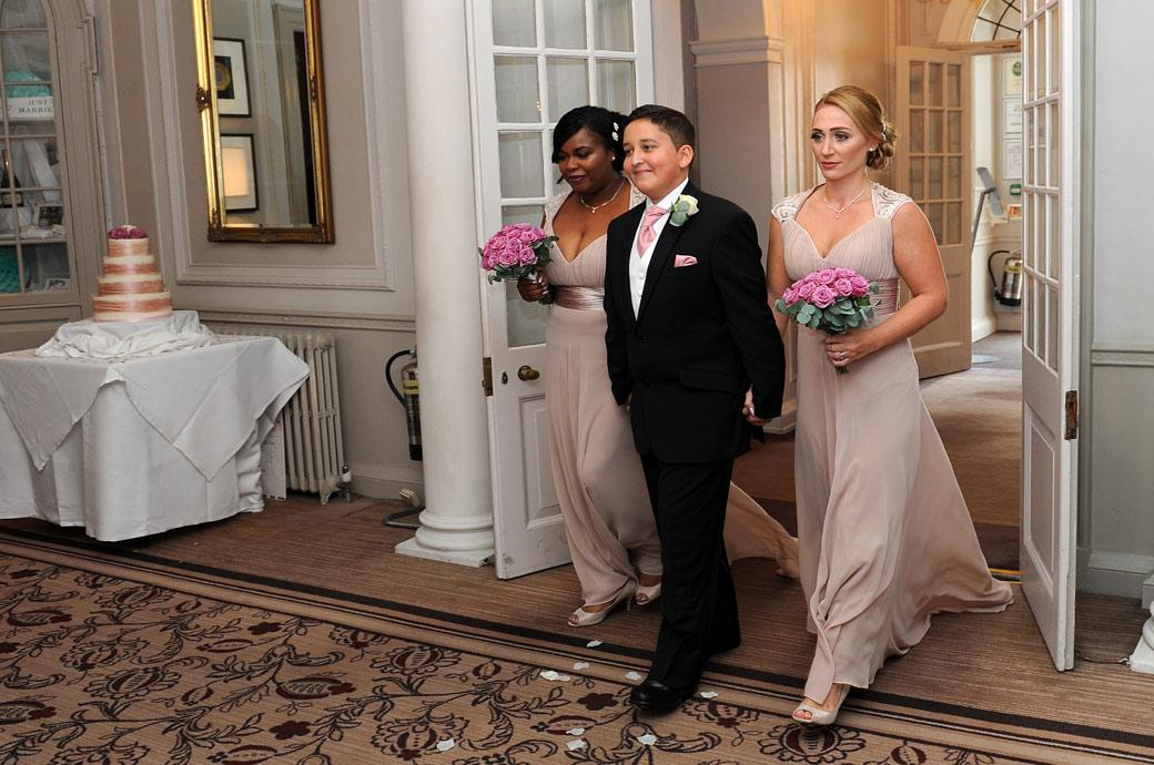 Lovely wedding photo of a smiling young groomsman being escorted by two bridesmaids into the marriage ceremony room at Gorse Hill a fine wedding venue near Woking in Surrey
