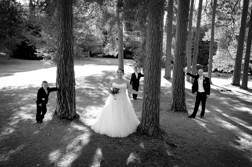 Bride and Groom having fun with their two smart looking boys at Surrey venue Gorse Hill Woking captured in this wedding picture taken in the tranquil grounds under the trees