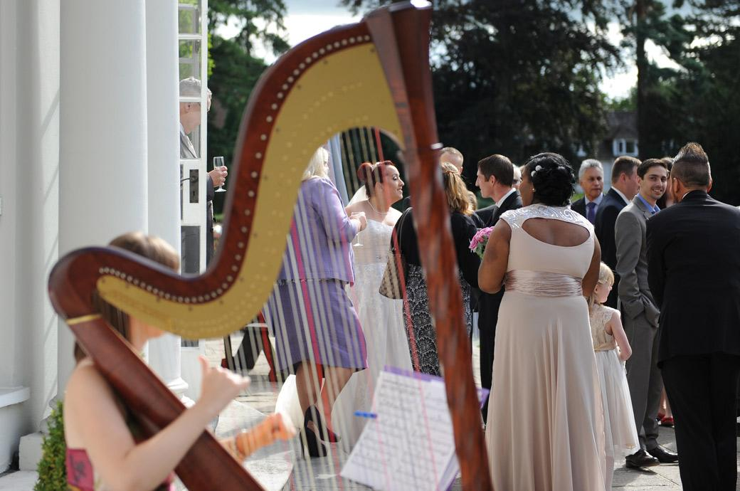 Peep view wedding photograph of the Bride talking to guests taken through the strings of the musician's harp captured in Surrey at Gorse Hill out on the patio