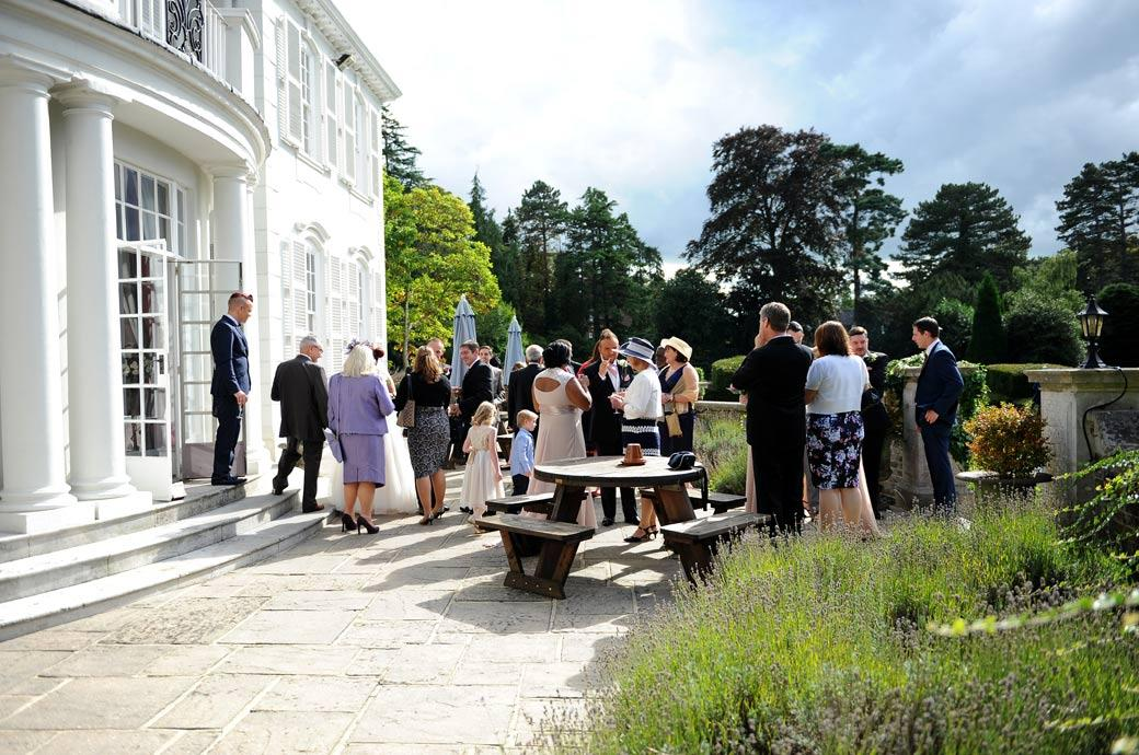 Wedding picture taken of guests talking over drinks on the patio during the reception on a sunny afternoon at Gorse Hill a fine classic wedding venue in green and leafy Surrey