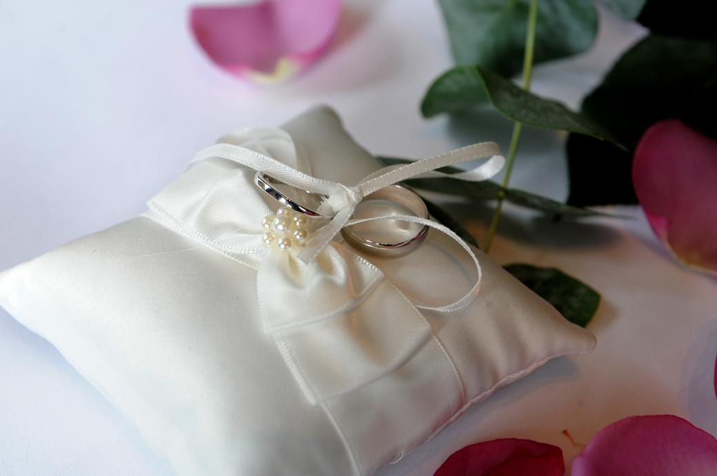 A close up photograph of the wedding rings tied to a cushion sitting amongst rose petals on the marriage ceremony table in the lounge at the Gorse Hill wedding venue in Surrey