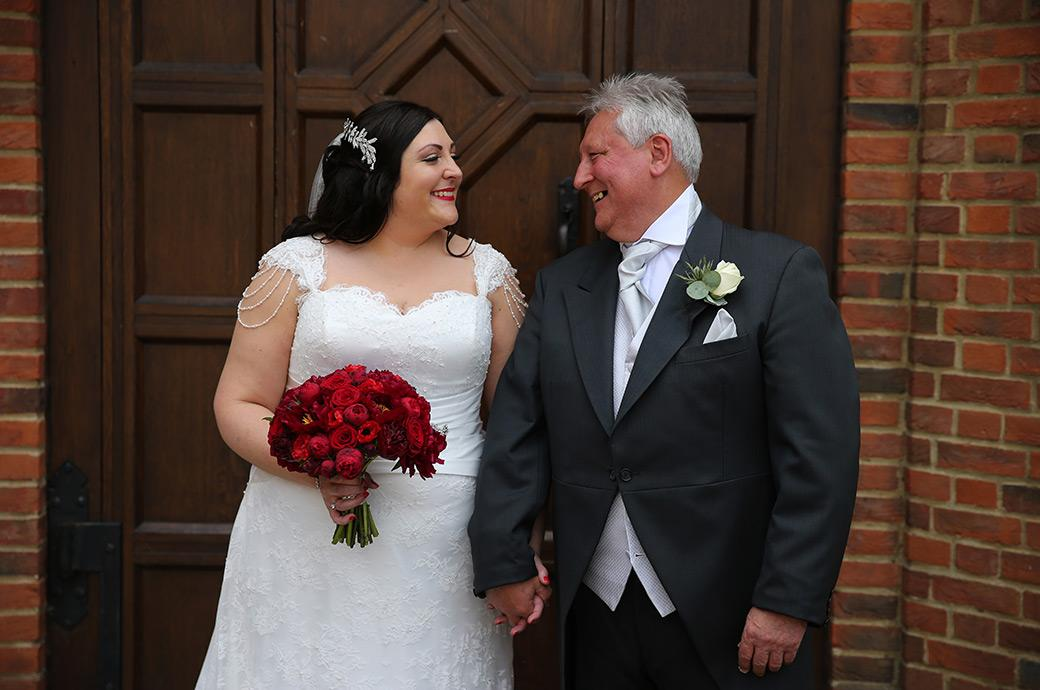 A sweet wedding picture of the Bride and her father smiling at each other before they enter The Orangery for the marriage ceremony at Great Fosters in Egham Surrey