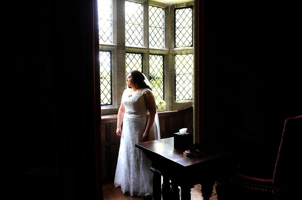A nervous Bride on her marriage day at the stunning Great Fosters Hotel in Egham Surrey looks from the window of the Tapestry Room down to the front entrance
