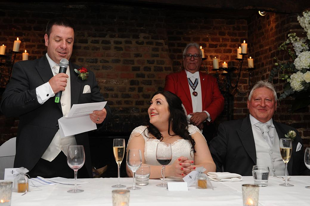 The Groom  at Great Fosters wedding venue in Egham Surrey gets his Bride and her father smiling on the top table in the Tithe Barn during his entertaining wedding speech
