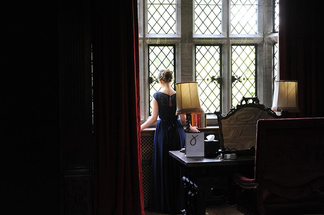 Wedding picture of the back of a bridesmaid at Surrey wedding venue Great Fosters Egham as she looks out the window of The Tapestry Room at the arriving wedding guests