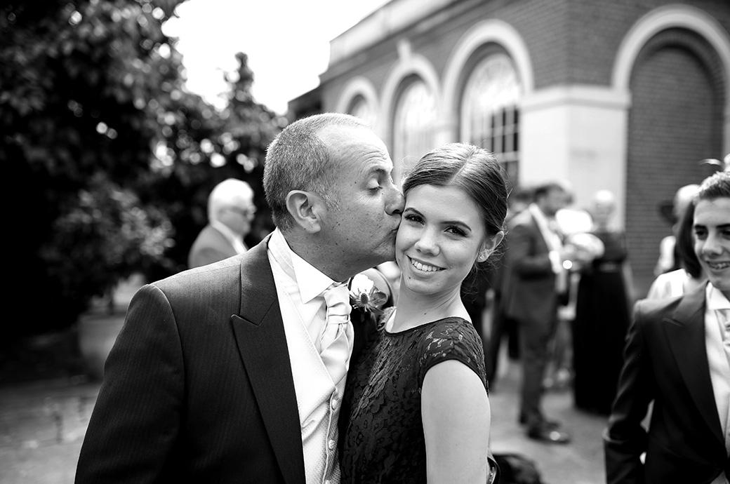 Light hearted wedding photo taken at Surrey wedding venue Great Fosters of a father kissing his young bridesmaid daughter during the drinks reception out on the sunny terrace