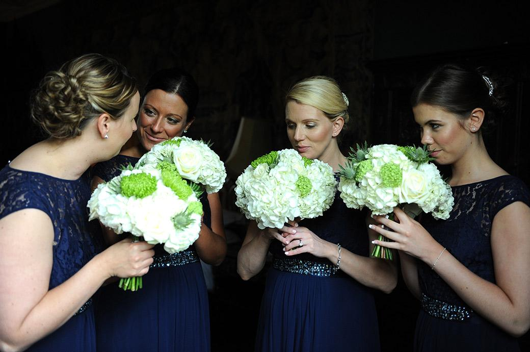 Bridesmaids in this wedding picture taken in the majestic Tapestry Room at the Grade One Listed Great Fosters Hotel in Egham Surrey smelling their lovely bouquets