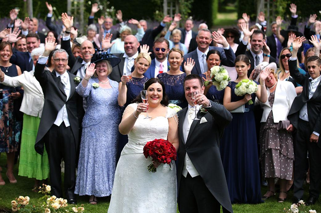 Smiling Bride and Groom raise their glasses of champagne as everyone at the wedding waves to the photographers at Great Fosters Surrey from the sunken circular rose garden