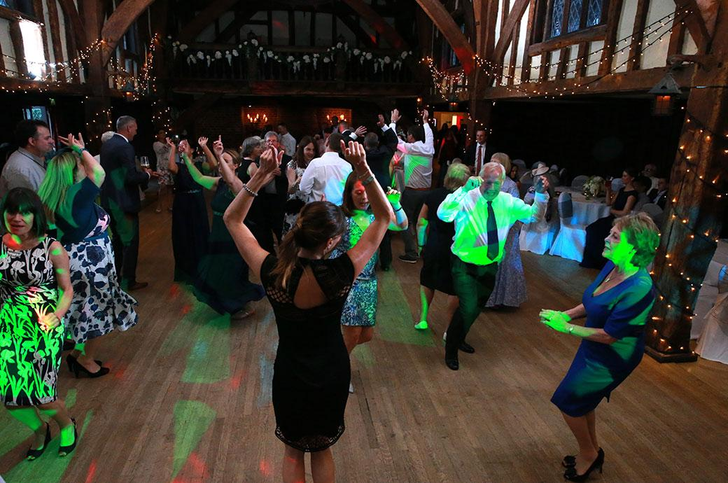 Wedding picture of fairy lights and disco lights and hands up in the air captured on the lively dance floor at Surrey wedding venue Great Fosters in the atmospheric Tithe Barn
