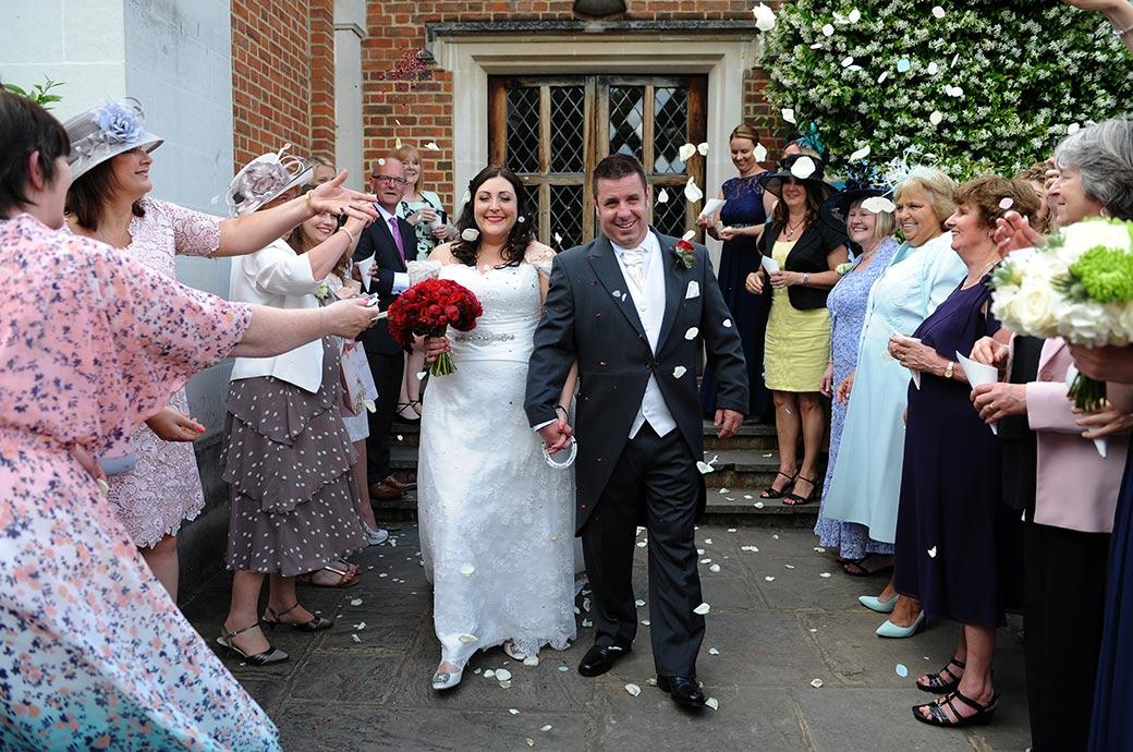 A confetti strewn Bride and Groom still smiling as they walk along the line of confetti throwers on the terrace at the wonderful Great Fosters a truly magical Surrey wedding venue