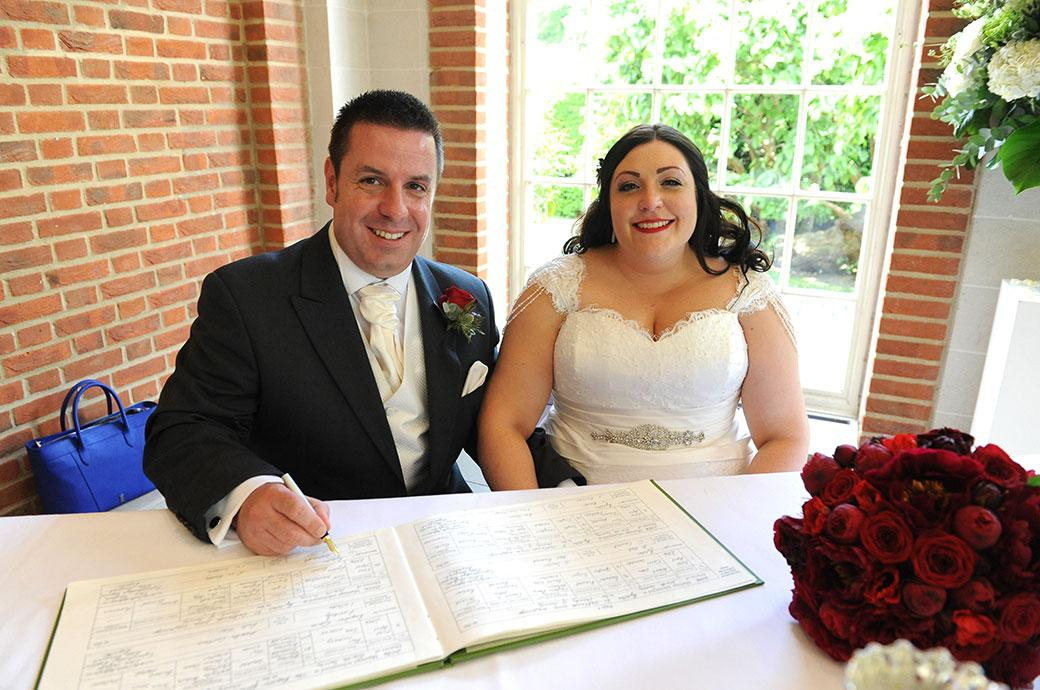 Beaming happy newlywed couple pose for the Surrey Lane wedding photographer as they sign the marriage register taken in The Orangery at Great Fosters wedding venue in Surrey