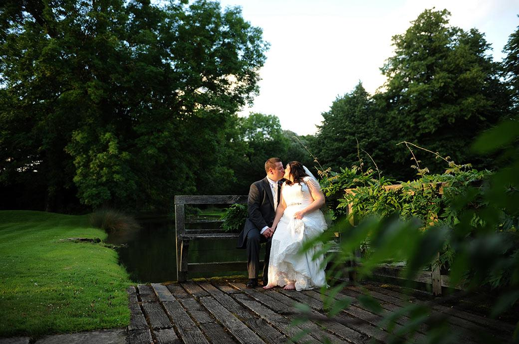 A romantic kiss captured in the beautiful grounds of Great Fosters in Egham Surrey as a newlywed couple sit on a bench by the Saxon Moat as the sun sets holding hands