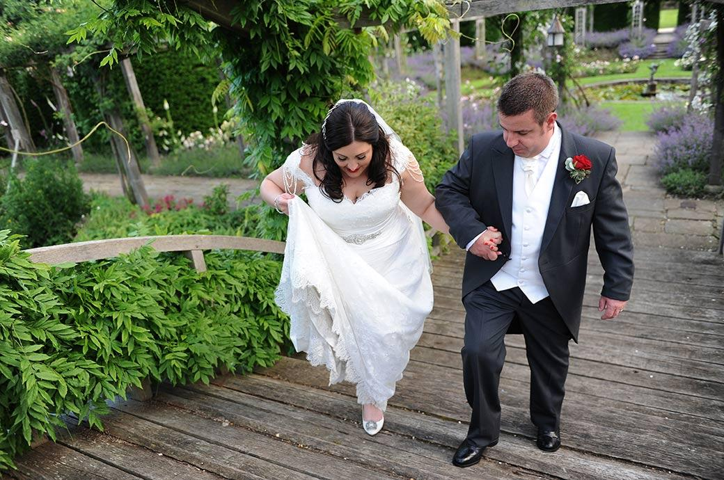Wedding picture of the Groom helping his Bride at the stunning Great Fosters venue in Egham Surrey as they ascend the rather steep wisteria covered Japanese Bridge