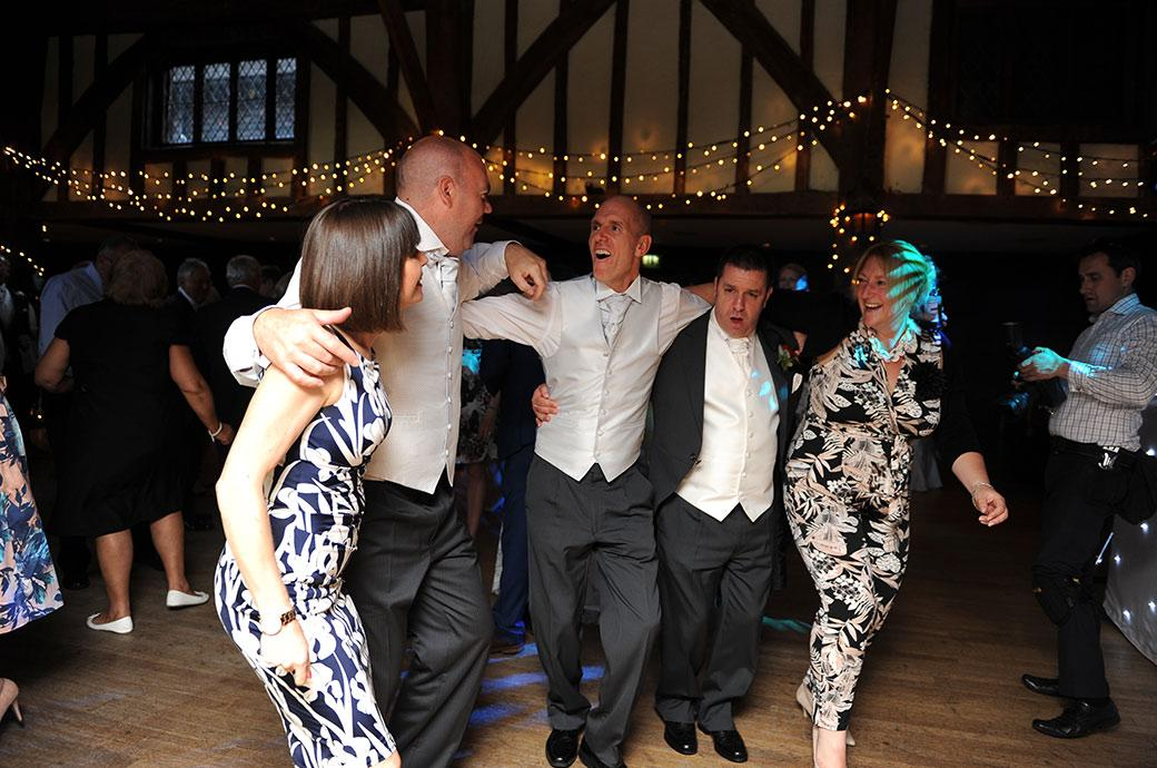 Groom and groomsmen involved in lots of singing and dancing during the evening festivities  at Great Fosters Egham Surrey on the Tithe Barn dance floor
