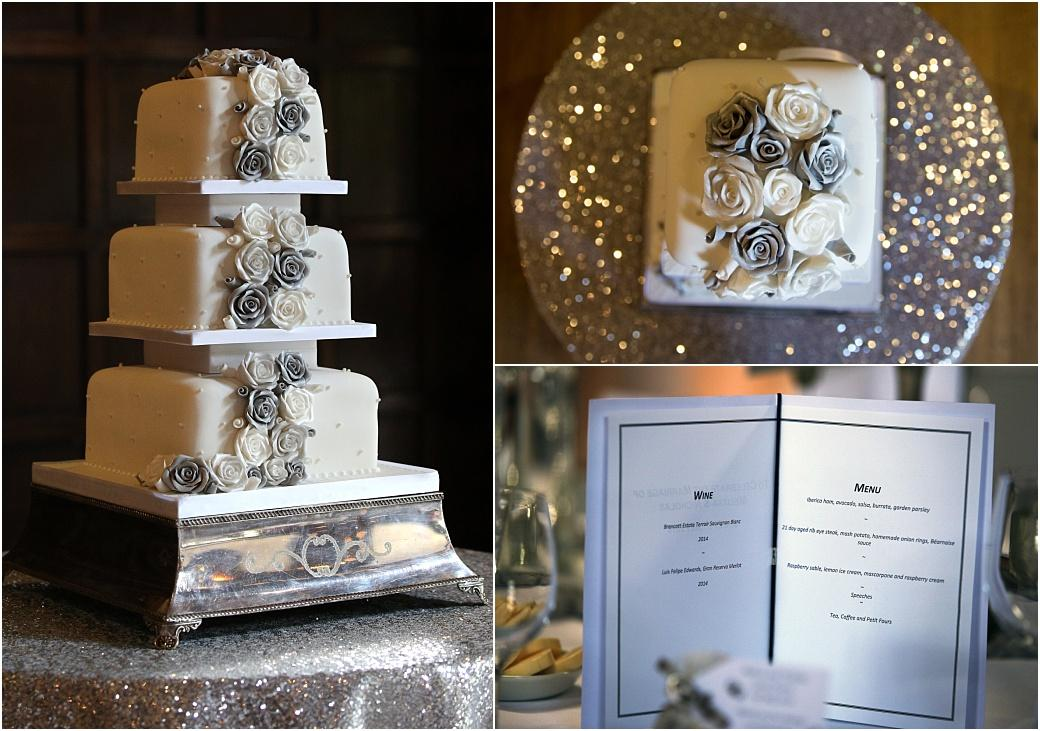 Views of a menu and an elegant wedding cake in the Tithe Barn at Great Fosters Hotel in Egham Surrey sitting on a silver base and decorated with white and silver flower decorations
