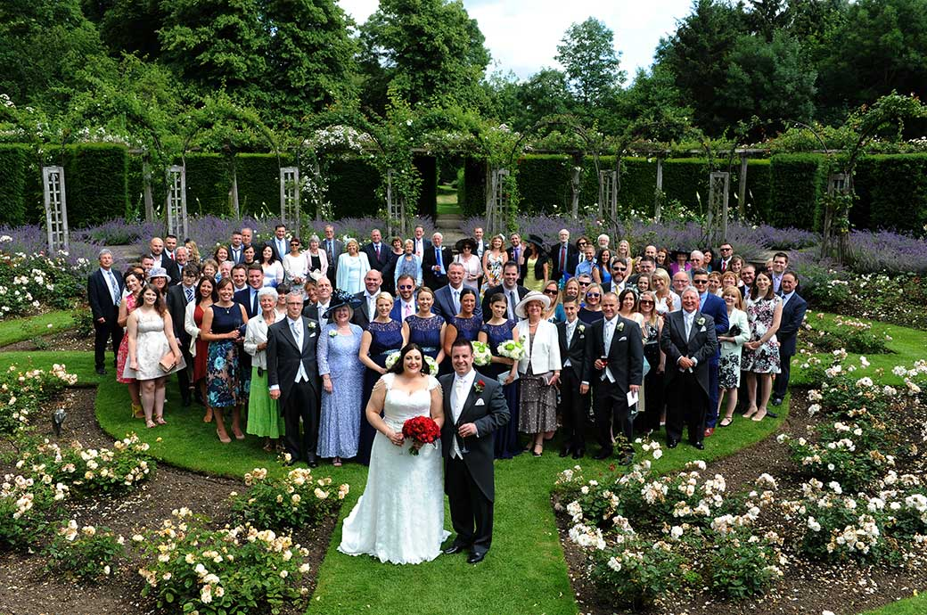 All smiles as the Bride and groom along with their guests pose for the popular everyone at the wedding picture taken at Surrey venue Great Fosters in the sunken circular rose garden
