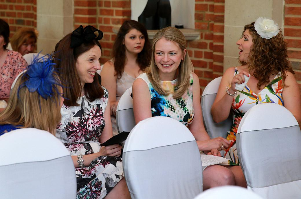 Excited lady guests in colourful summer dresses have a chat and a laugh in The Orangery at the wonderful wedding venue Great Fosters in Surrey as they await the arrival of the Bride