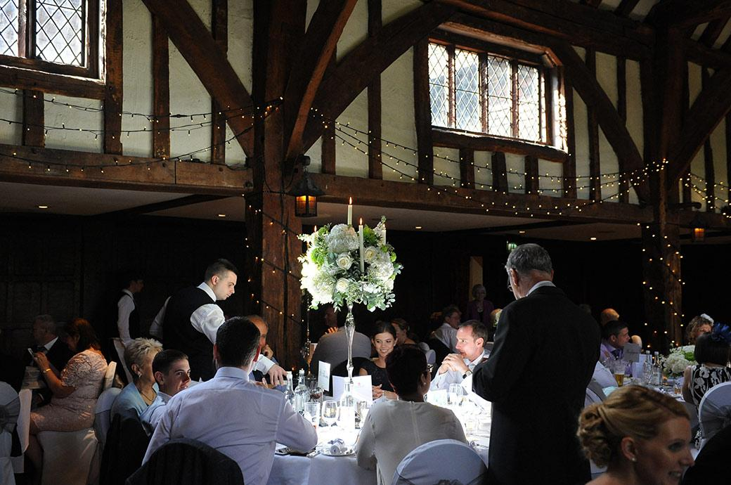 The atmospheric scene captured here in this wedding photograph from the ancient Tithe Barn at Great Fosters in Egham Surrey as the waiters pour the champagne for the speeches