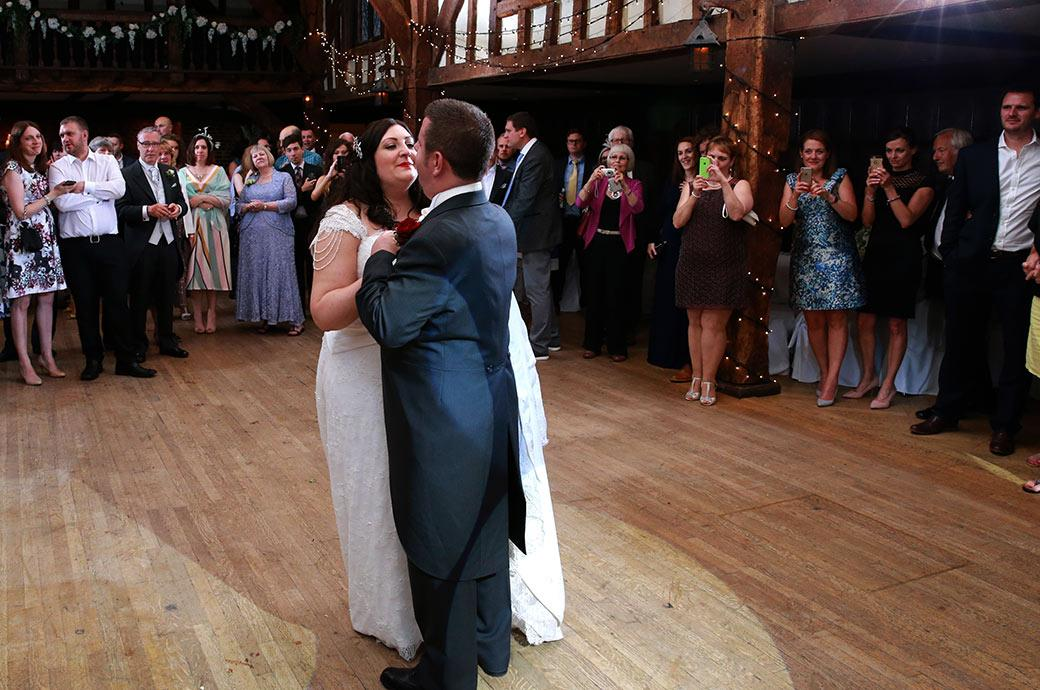 Bride and Groom start their first dance in the middle of the dance floor in the Tithe Barn at  Great Fosters in Surrey as guest watch on with their camera phones at the ready