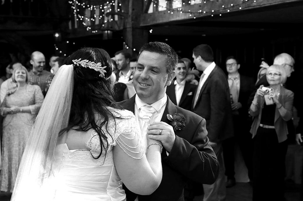 Happy content and smiling Groom holds his wife's hand in their first dance captured at the wonderful Surrey wedding venue Great Fosters in the atmospheric Tithe Barn