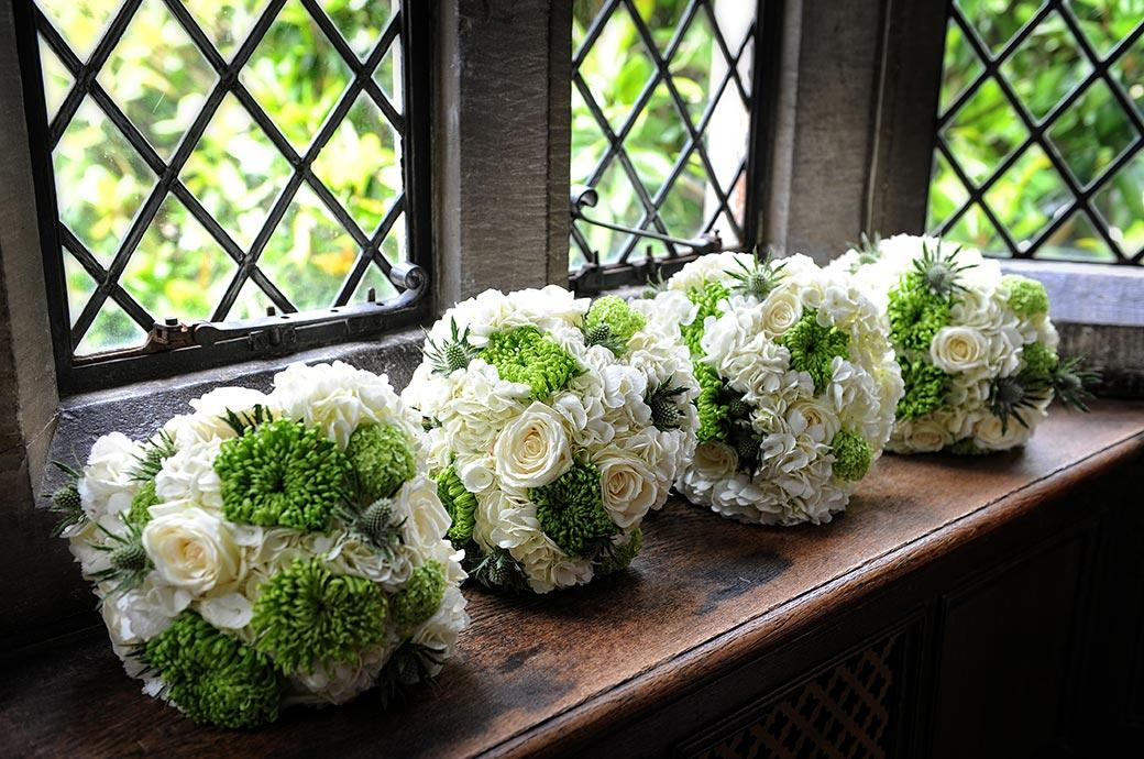 A wedding photograph of four bright and fresh bridesmaids' bouquets sitting in the window of The Tapestry Room at the Great Fosters wedding venue in Egham Surrey