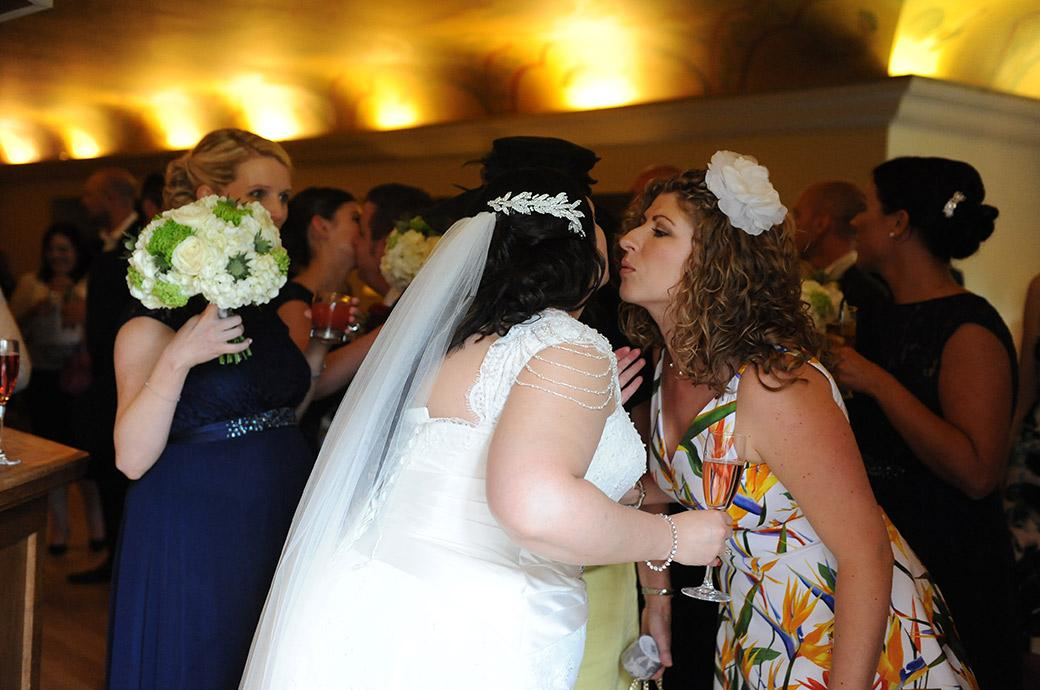 Bride with celebratory champagne in hand after her marriage at the wonderful Surrey wedding venue Great Fosters in Egham moving to kiss a guest in the Painted Hall