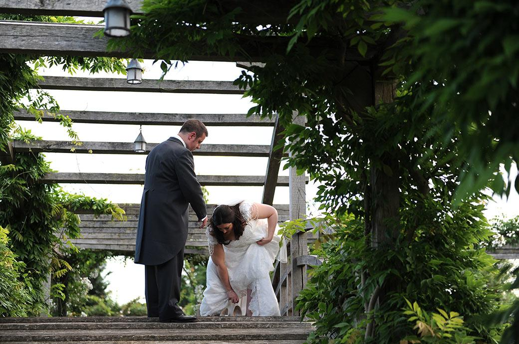 Groom waits for his Bride as she takes off her wedding shoes on the charming wooden Japanese Bridge at Great Fosters in Egham a stunning Surrey wedding venue