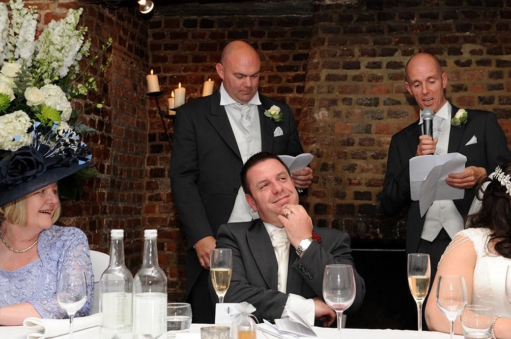 The smiling Groom captured at Great Fosters Tithe Barn in Surrey during the funny speeches visibly thinking about the highly fictitious words spoken by his best men