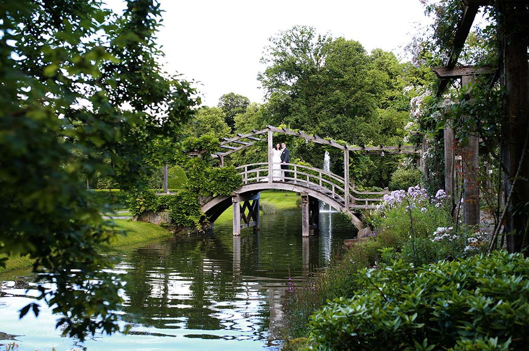 Long distance wedding photo of the newlywed couple in the beautiful gardens of Great Fosters in Egham Surrey standing on the delightful Japanese Bridge covered in wisteria