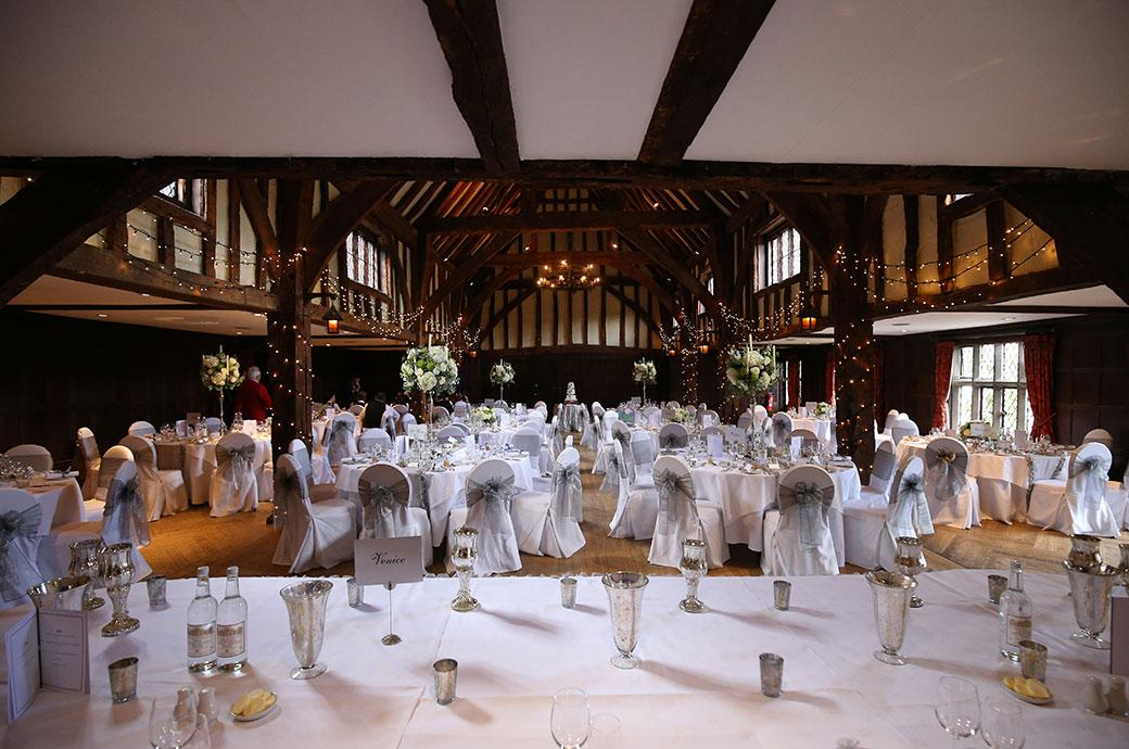 View of the fabulous wedding breakfast settings taken from under the minstrels gallery in the ancient Tithe Barn at Surrey venue Great Fosters Egham