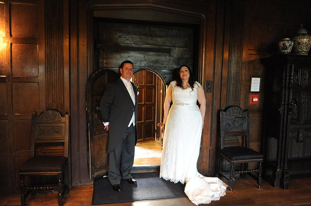 Smiling newlywed couple at the magnificent Surrey wedding venue Great Fosters in Egham proudly standing by the wicket of the stout oak front door opening to the Great Hall