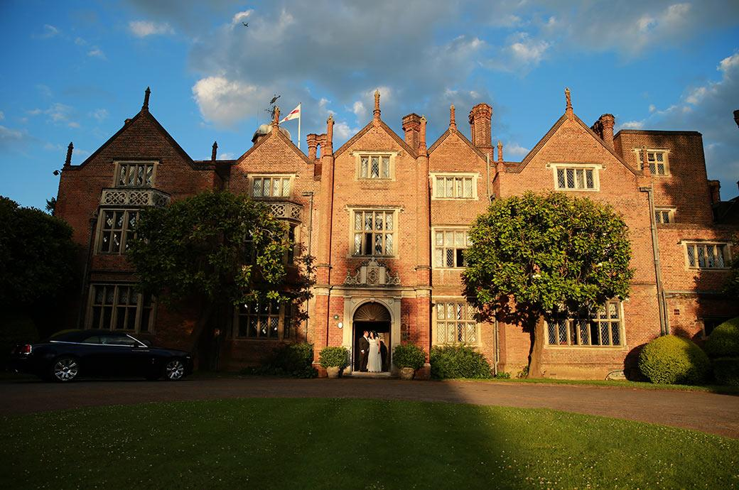 Newlyweds captured in this wedding photo standing in the doorway to the main entrance of Surrey wedding venue Great Fosters in Egham in the last rays of the setting sun