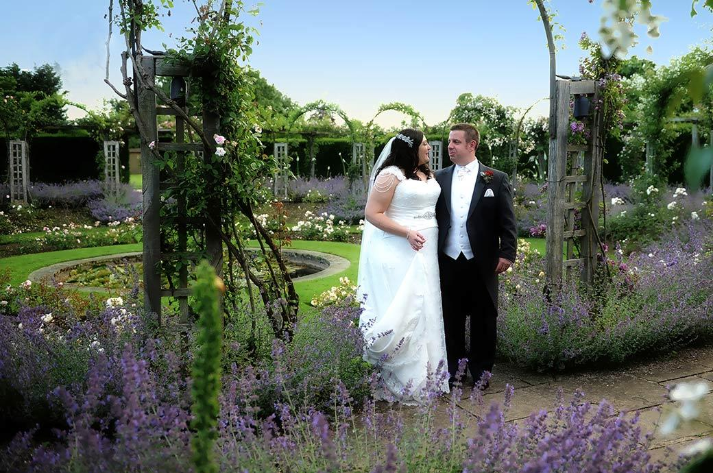 Bride and groom stop and take time to talk in the beautiful sunken rose garden during a romantic walk around the magnificent grounds of Great Fosters in Egham Surrey