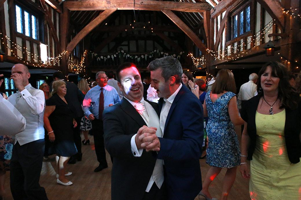 The Groom having fun and dancing with another man on the packed dance floor at Great Fosters in Egham Surrey during the night time wedding reception celebrations