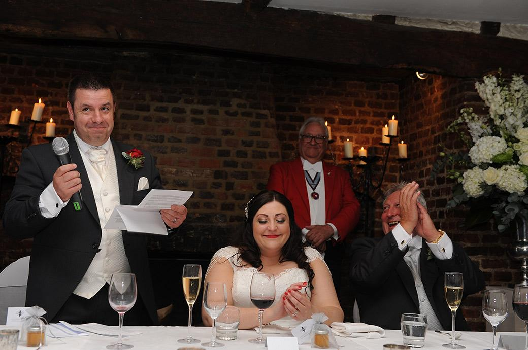 A smiling Groom in The Tithe Barn at Great Fosters in Egham Surrey finishes his wedding speech with true aplomb and gets hearty applause from his Bride and her Father